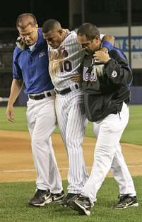 New York Mets trainers walk a hamstrung Endy Chavez off the field.