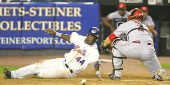Lastings Milledge slaps the plate ahead of the tag to score the winning run for the Mets