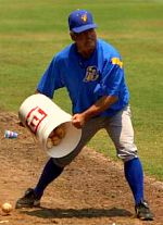 Wally Backman of the South Georgia Peanuts throws baseballs onto the field in a game against the Anderson Joes